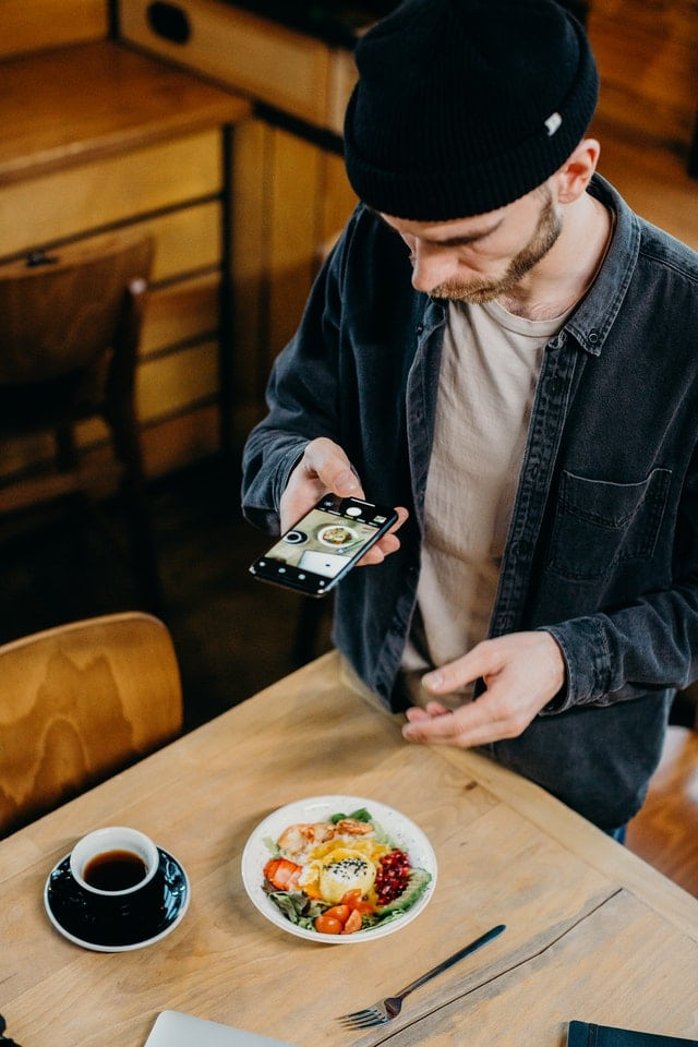 man taking picture of food with phone