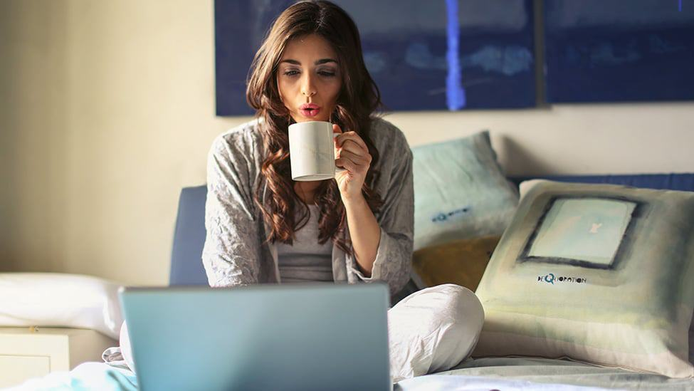 woman on computer drinking coffee
