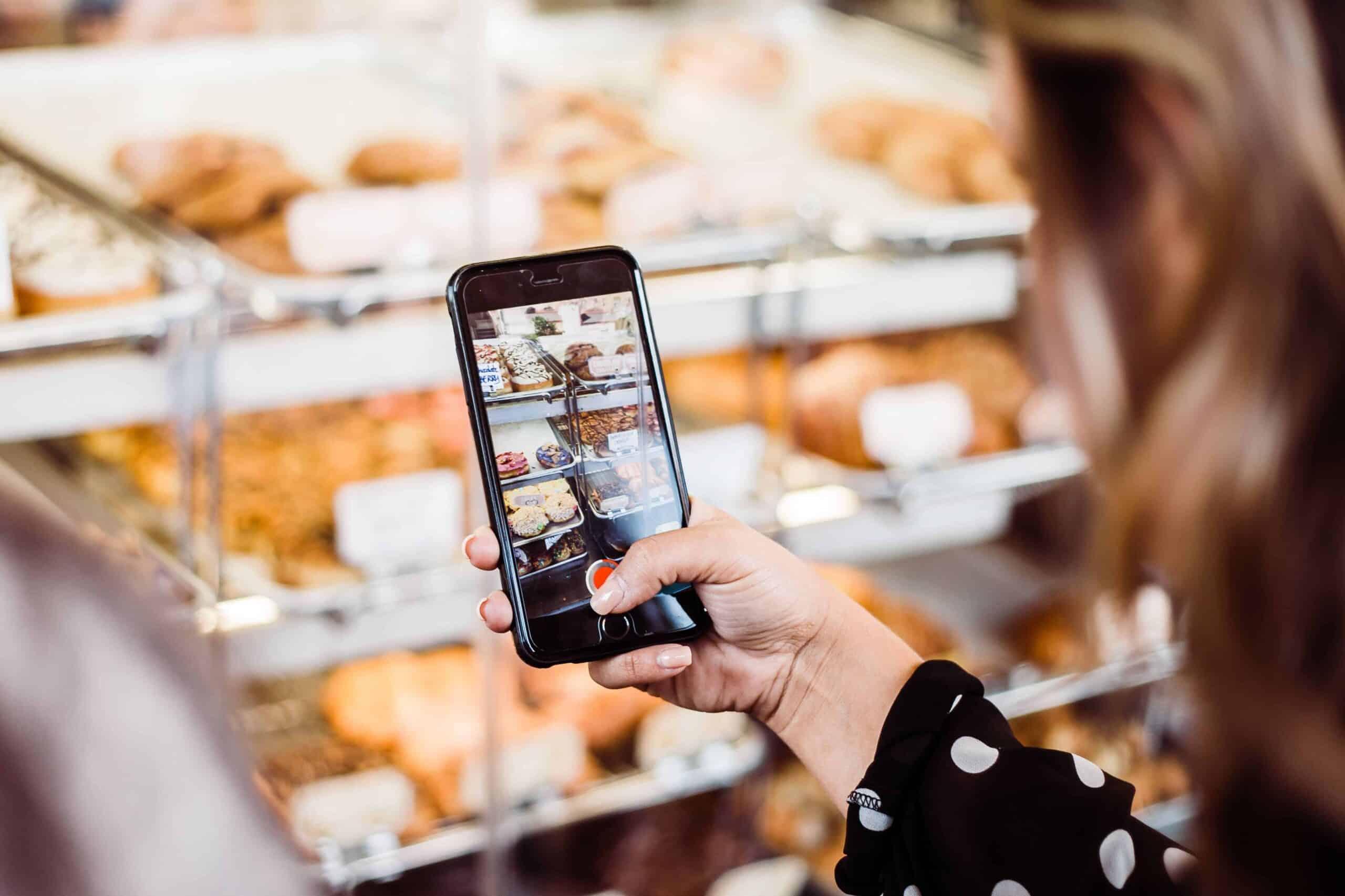 woman-taking-photo-of-food-display