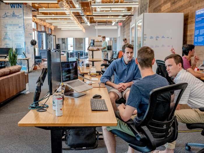 three men talking at a desk at their social media marketing agency