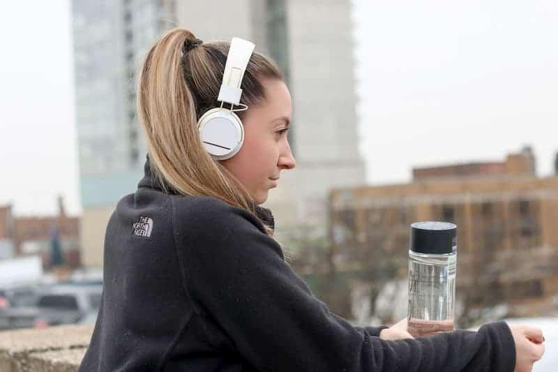 woman outside wearing white headphones